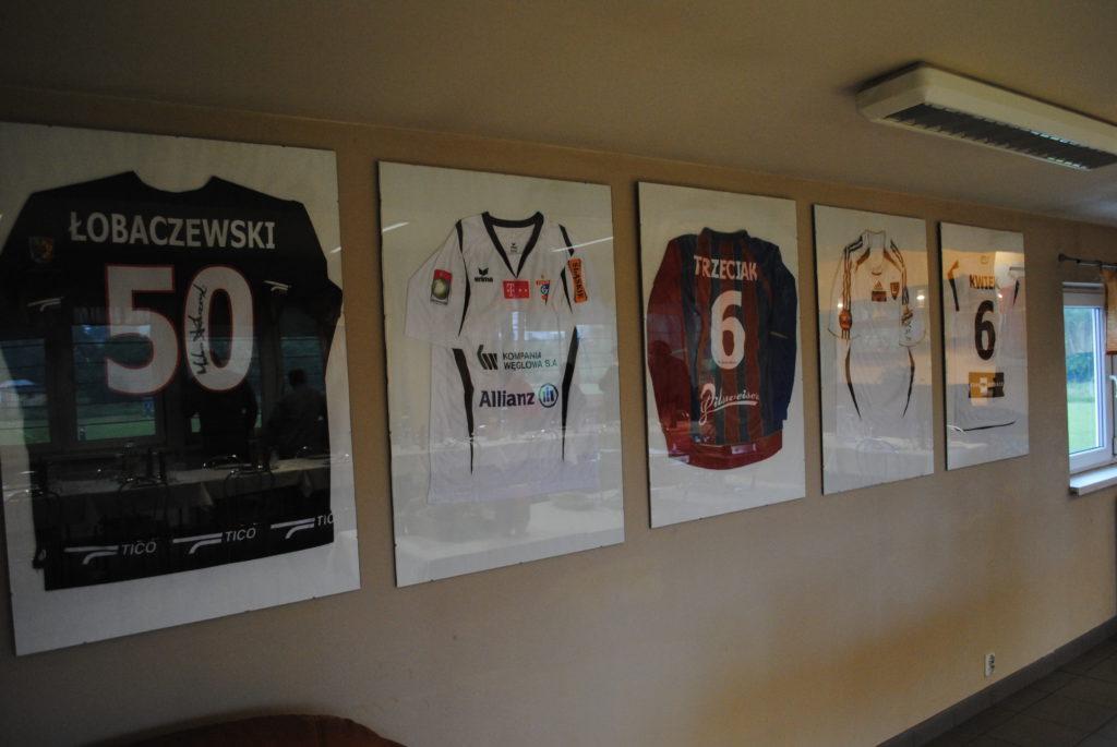 Koszulki byłych graczy Rymera w antyramach na ścianie