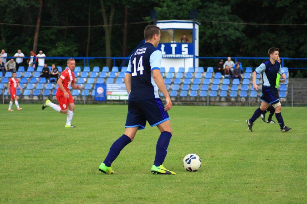 Zawodnik Rymera przy piłce na boisku ŁTS Łabędy. W pobliżu jego kolega z drużyny i przeciwnicy z ŁTS. W tle kibice na niebieskich krzesełkach i wieżyczka komentatorska.