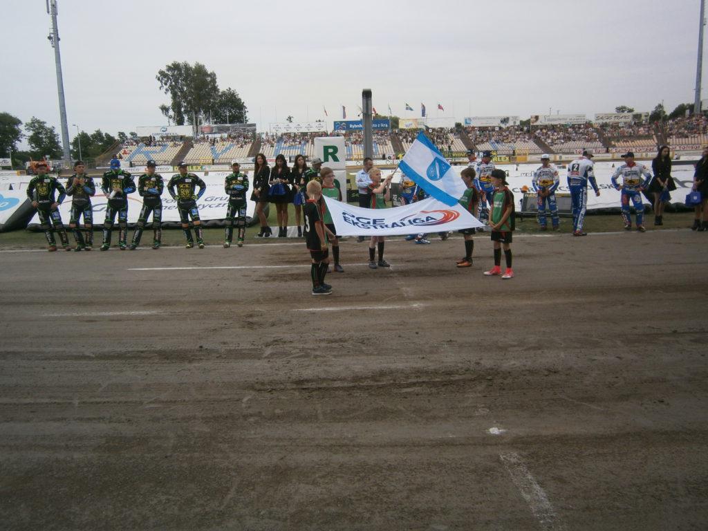 Chłopcy z Rymera z flagą głównego sponsora PGE Ekstraliga i Miasta Rybnik na stadionie ROWu