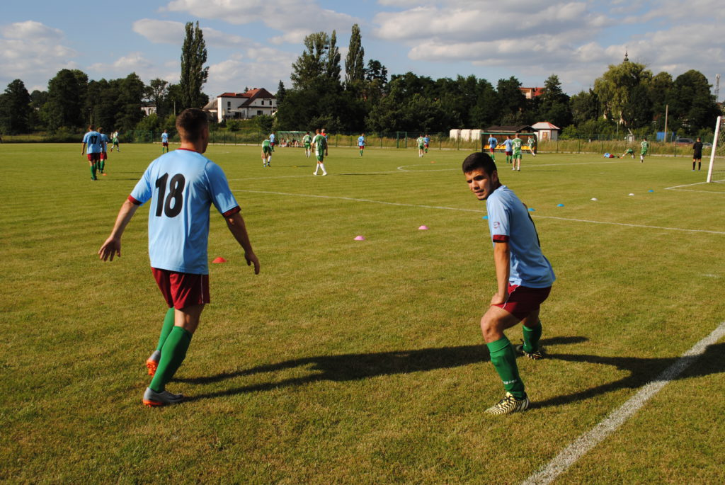 rezerwowi piłkarze Górnika Boguszowice rozgrzewają się. w tle piłkarze na murawie