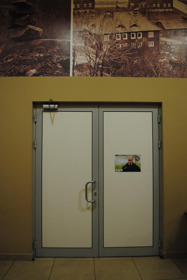Drzwi z plakatem zapraszającym na spotkanie z Jackiem Trzeciakiem. Powyżej zdjęcia z Niedobczyc.