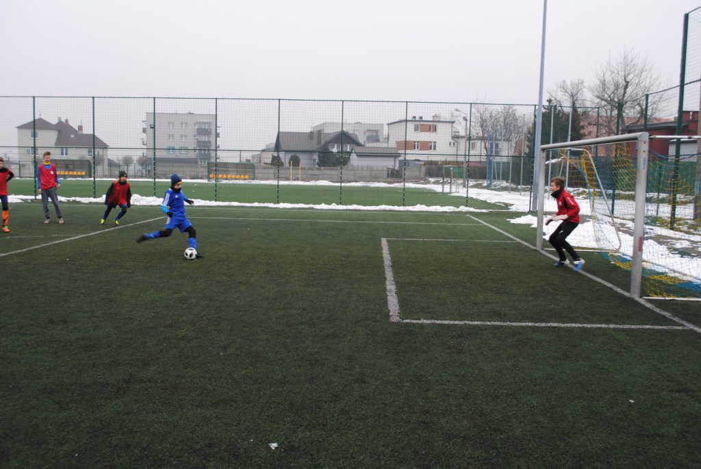 chłopcy kopią w piłkę na Orliku