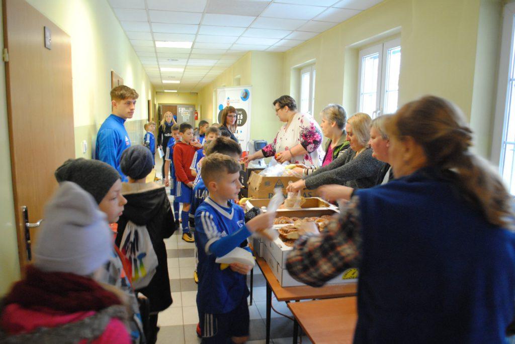 Wolontariuszki ze Stowarzyszenia Nie dla Nudy rozdają owoce i bułki