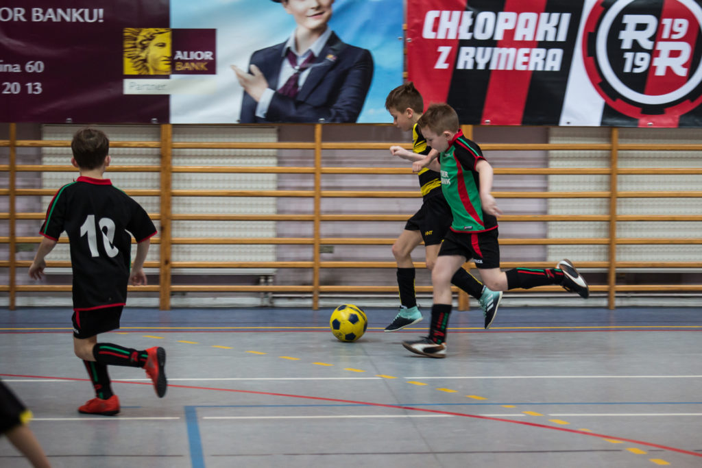 chłopcy kopią w piłkę na hali