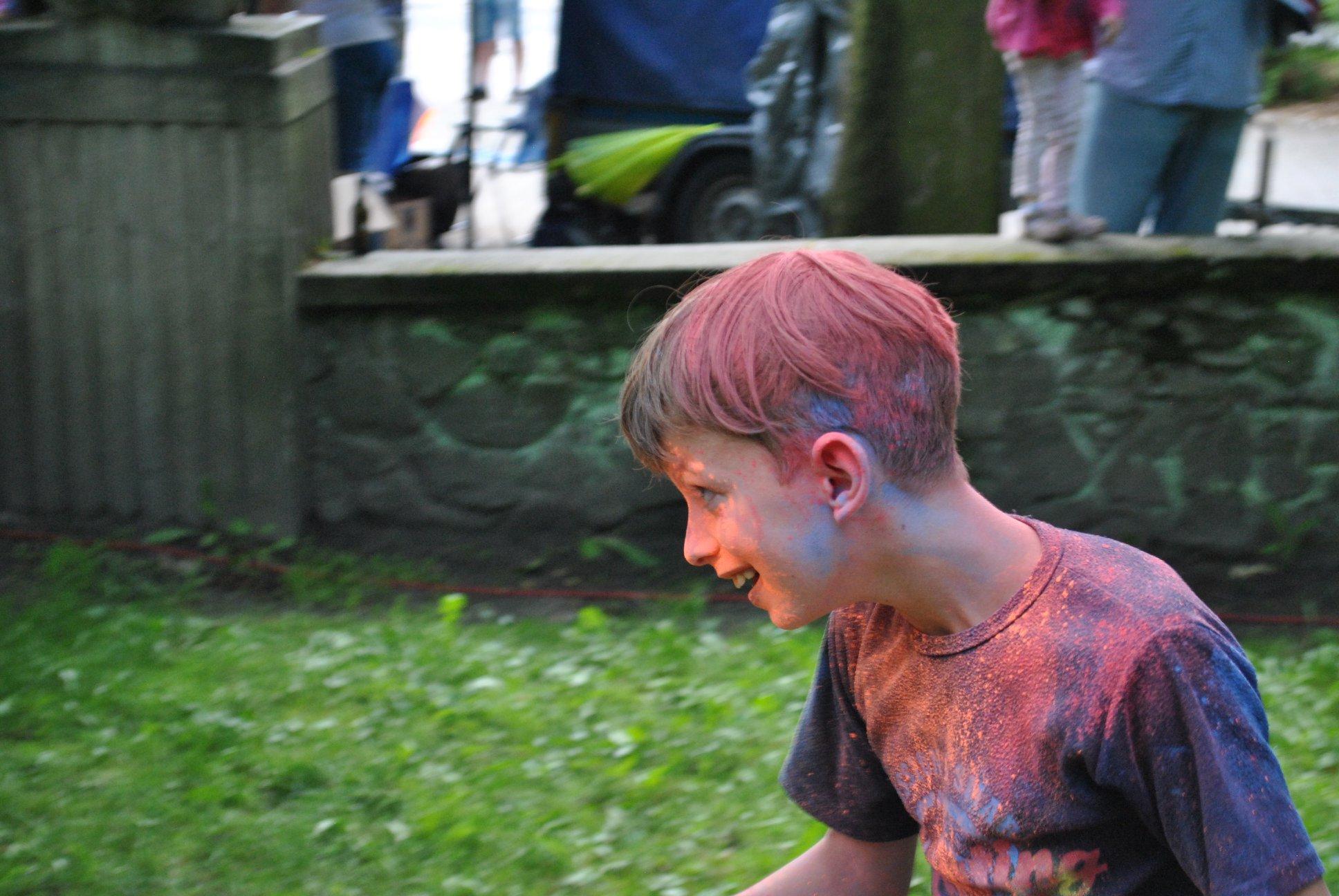 chłopiec w czasie zabawy rzucaniu proszku holi